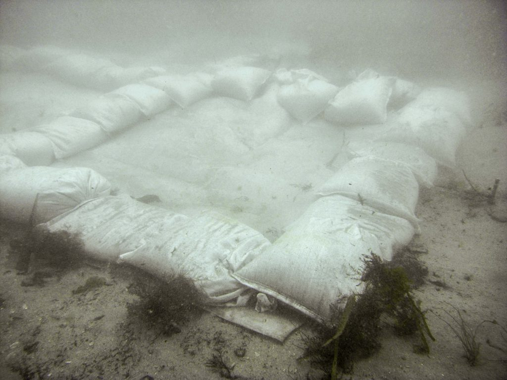 A rectangle of sandbags on the seabed